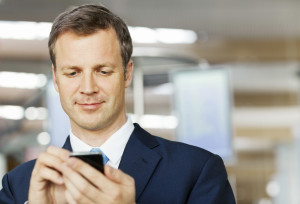 Handsome corporate businessman text messaging on smart phone. Horizontal shot.